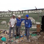 Officials of the Mukuru Brotherhood outside of their pig project structure. Photo credit: Elaine Jones.