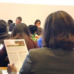 "Audience members at ILC reading WIEGO's position paper, ""Waste Pickers: The Right to be Recognized as Workers."" Photo: Lucia Fernandez."