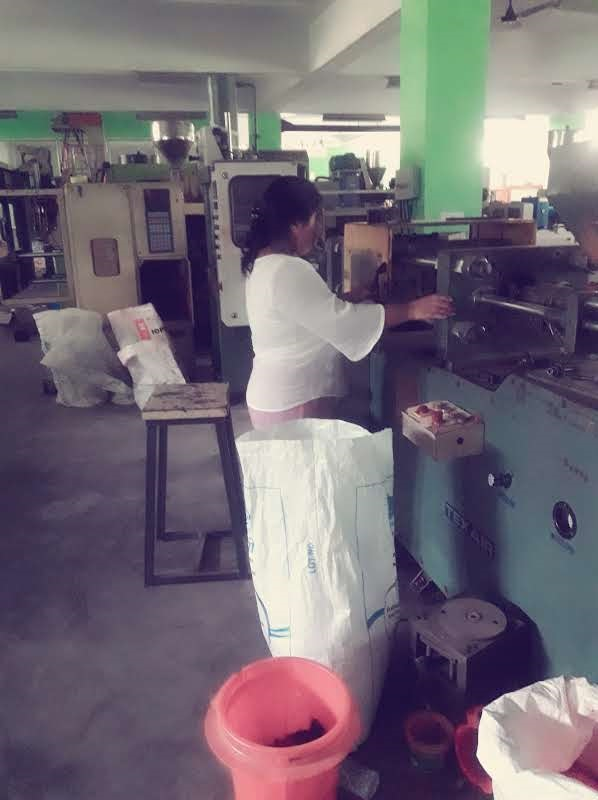 Ibapynhunshisha Kharnaior operating a plastics manufacturing machine