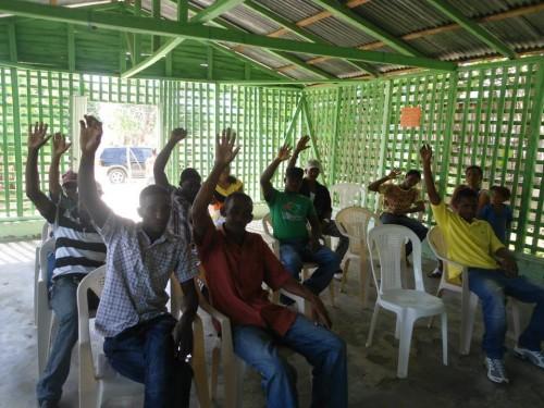 Membros da associação de catadores da República Dominicana levantam as mãos em uma votação durante a conferência. (Foto: Felipe Rosario)